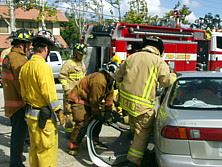 Firefighters pull open the door of the vehicle to remove the injured driver