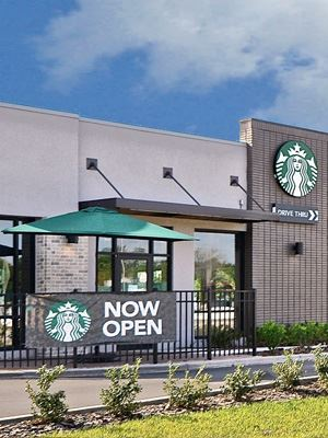 "Starbucks Coffee Shop with a grey facade, and a black banner with white ""Now Open"" text."